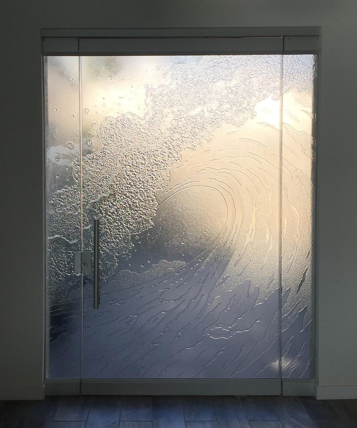 Cast glass entryway door with cresting wave motif